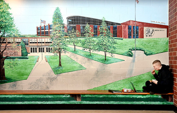 Anderson High School junior Gage Huff finds the bench along one of the big murals in the entryway of the high school is a good place to spend a quiet lunch Monday and to work on his laptop.
