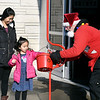 Resamae Due watches as her daughter Haylee, 5, puts a donation into the red kettle as Salvation Army bell ringer Jan Presley holds it for her Tuesday at the grocery entrance to Walmart in Anderson.