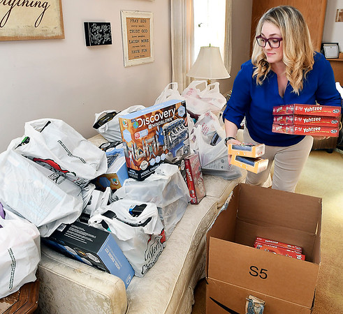 Operation Love Ministries executive director Andrea Baker sorts out the bags and boxes of gifts for children as the organization gears up for their Christmas Wishes Program which has 300 families registered for the program.