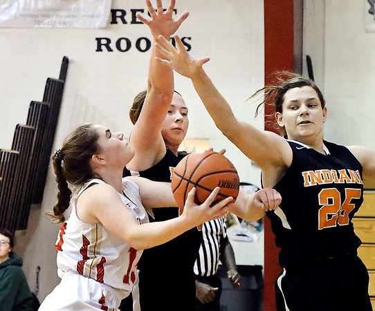 Liberty Christian's Mady Rees drives the lane for a shot as Indiana Deaf's Hannah Puent and Anya Pothorski try to block.