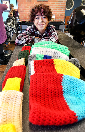 Malaki Huffer, 12, with some of the hats and ear warmers his has crocheted to give to the homeless for the holidays.