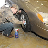 Dylan Wable cleans the wheels on a car at Smith's Attention to Detail auto detailing shop.