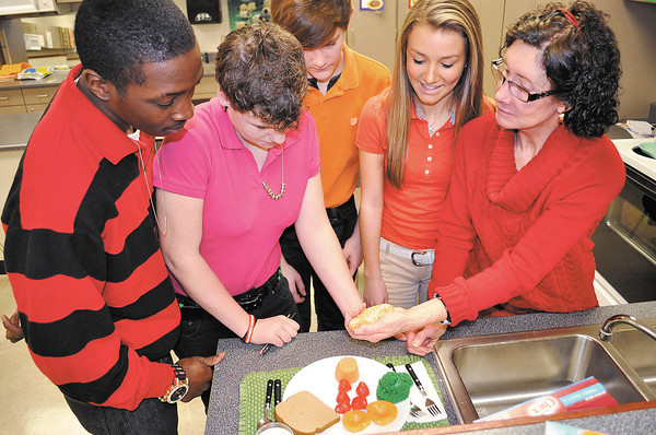 Highland 8th graders from left, Deontré Smoots, Emma Simer, Michael Tupling and Emma Strangeway are shown easy ways to determine portion size by Family and Consumer Sciences teacher Cynthia Blowers.