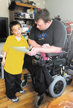 Tim Senkowski talks to his son Dustin about his school work as he arrived home from school. Senkowski is home on leave from Walter Reed National Military Medical Center where he has been recovering from severe wounds caused by an improvised explosive device in Afghanistan.