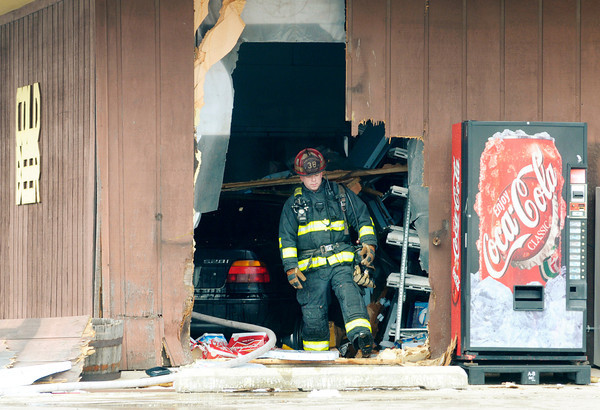 Chesterfield Union-Township Fire Chief Jamey Burrows steps through the hole created in the front of Sixty Nine Liquors after a car drove through the front of the business at exit 234 in Daleville on Tuesday afternoon.