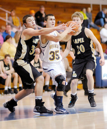 Shenandoah's Moose Kirk drives between Lapel's Brady Cherry (32) and Bailey Partington (20) as he scores a layup on Thursday.