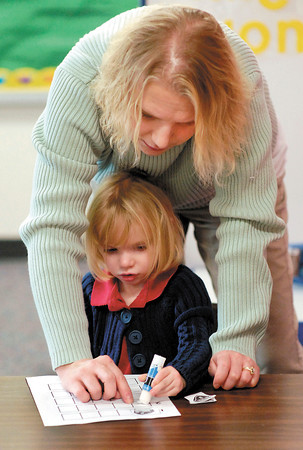 Anderson Elementary developmental preschool teacher Michelle Ray assists student Jocey Marvin as she pastes symbols onto a numbers sheet.