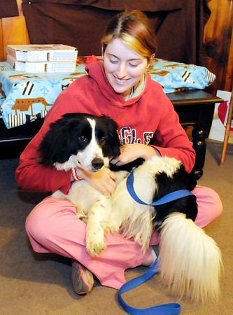 Lauren Caldwell with the Madison County Humane Society holds Peetey, a Border Collie Basset Hound mix, as Ernie's Heart Pet Food Pantry celebrated opening in their new location on Thursday. Peetey is one year old and up for adoption.