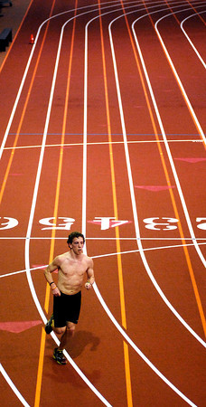 Eric Linn, a member of the Anderson University track team makes his rounds on the indoor track in Kardatzke Wellness Center Tuesday as the cold, damp weather prevented any outdoor training.