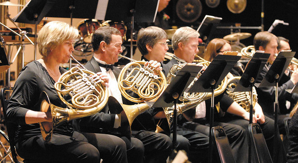 The Anderson Symphony Orchestra french horn section on stage at the Paramount Theatre Centre.