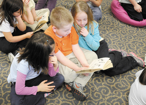 "From left, Jasmine DeMarco, William Scarberry and Sierra Stevens follow along as their teacher Kristi Worley reads the book ""Mr. Popper's Penguins"" on Thursday."