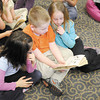"From left, Jasmine DeMarco, William Scarberry and Sierra Stevens follow along as their teacher Kristi Worley reads the book ""Mr. Popper's Penguins"" on Thursday."