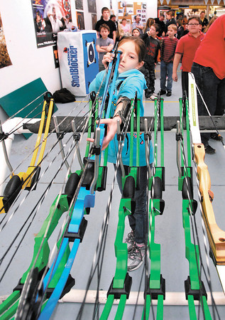 Karissa Hall, 10, from Frankton, picks out a bow from the rack on the first night of Madison County 4-H archery lessons Monday held at Girt's Archery in Anderson.  The class, for kids between 8-18 years old, runs six weeks long and they had 86 4-H'ers sign up for this years' two sessions.