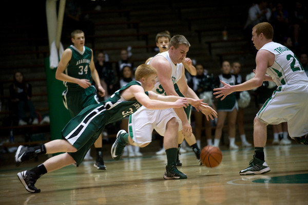 Pendleton Heights' Austin Brizendine dives to challenge New Castle's Kyle Goolsby and Steven Bennett for a loose ball. Pendleton Heights High School defeats New Castle at the fieldhouse 61 to 60 Tuesday, February 12, 2013. Photo by Richard Sitler