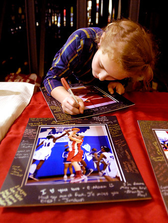 Emma Allen, 9, a 4th grader at Liberty Christian School leaves a note on one of the framed 8 x 10 photographs of the seniors honored Tuesday evening at Liberty Christian's Winter Sports Senior Night at their basketball game.