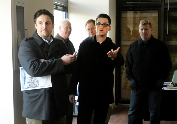 Auctioneer Ted Pike, left, and Mitch Doner scan the room for bids as Pike auctions the Tower Apartments on Wednesday. The winning bid of $100,000 was the only bid offered.