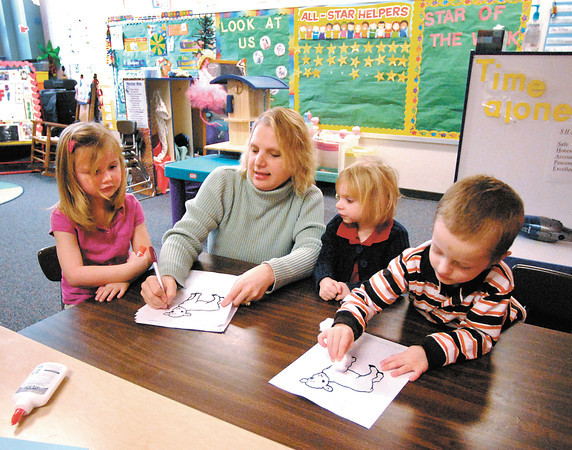 Anderson Elementary developmental preschool teacher Michelle Ray works with students Delaina Bickers, Jocey Marvin, and Landon McGuire on a art project in her afternoon class.