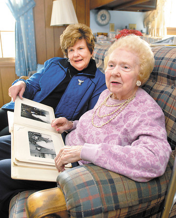 Home Instead Senior Care care giver Sandy Brizendine sits and talks with client  Phyllis  Magers as they look over a family photo album in the Magers' home.  Home Instead Senior Care now has a new location, new services and<br /> has been nominated for an award.