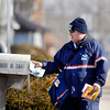 Mail carrier Jeff Fudge delivers mail along his route Wednesday down west 4th Street in Anderson.