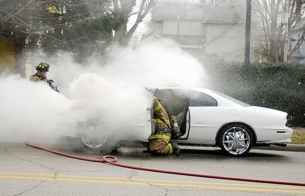 AFD fire fighters Mike Wallace, left, and Robin Branch put out a car fire on Eighth Street on Thursday. The occupants of the car were able to get out safely.