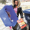 Robyn Thomas empties her family's recycling bin on Friday. Thomas will be going to Washington, D.C., to take part in an environmental conference over the Summer.