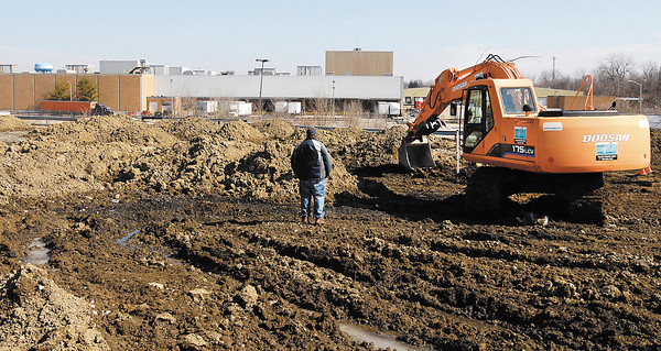 City workers move dirt in the parking lot in front of the old Guide Plant 9 on the East side of MLK.  The property owner, Racer Trust, is paying the city to remove the old parking lot and to create a green space along the city gateway.