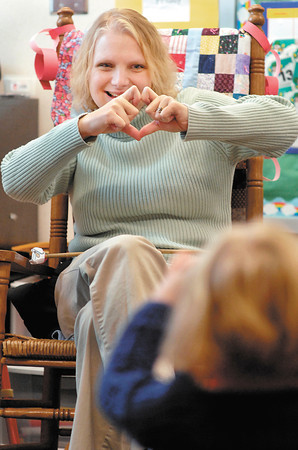 Anderson Elementary developmental preschool teacher Michelle Ray shows her students how to make a heart shape with your fingers.