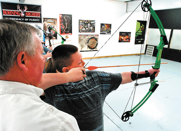 Jayden Kinsinger, 10, of Anderson, pulls back on his bow as Ron Hinton assists him on the first night of Madison County 4-H archery lessons Monday held at Girt's Archery in Anderson.  The class, for kids between 8-18 years old, runs six weeks long and they had 86 4-H'ers sign up for this years' two sessions.