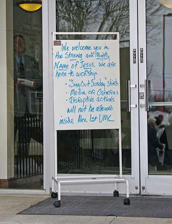 A sign posted outside the door of the Alexandria United Methodist Church states the condtions under which members will be admitted for Sunday worship services.