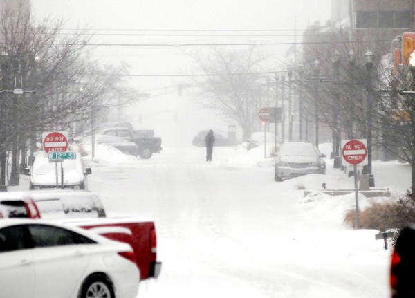 THB photo/John P. Cleary<br /> As the snow fell and visibility dropped  getting around on foot for some was the best option like this person walking down the middle of Meridian Street in downtown Anderson Tuesday afternoon.