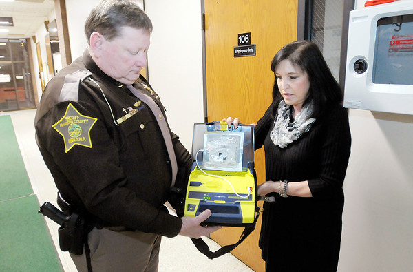 Don Knight / The Herald Bulletin<br /> RN Holly Renz and Sheriff Ron Richards look at one of the AEDs located in the Madison County Government Center. Equipping sheriff deputy vehicles with AEDs can make the difference between life and death on medical calls in rural parts of the county.