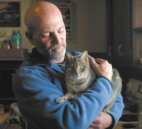 THB photo/John P. Cleary<br /> Brian Hudson, a former meth user, is going through Drug Court and getting his life back together.  Hudson, here with his favorite cat, Nanny, has five cats total living with him in his small Alexandria home.