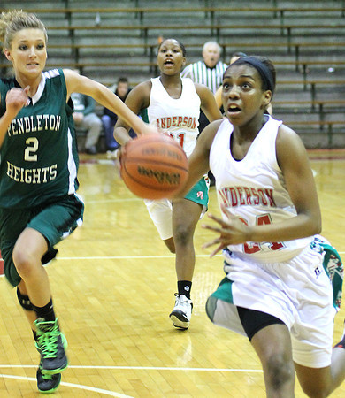 Photo by Chris Martin for THB<br /> Anderson's Debriona Williams drives past Pendleton's Kelsee Wendling Friday night in the sectional semi-finals.
