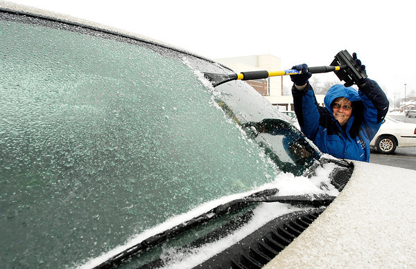 THB photo/John P. Cleary<br /> Rosie Beard, of Anderson, has to reach high as she scraps off the ice from the windshield of her pickup truck after getting off work Monday afternoon.  Beard, who works in a lab inside St. Vincent Anderson Regional Hospital, had a layer of ice greeting her from the freezing rain, sleet, and snow that fell over the area during the late afternoon hours.<br /> <br /> <br /> Cleaning off vehicles of the ice from freezing rain and sleet.