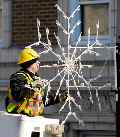 THB photo/John P. Cleary<br /> Joe Nuce, of Anderson Light & Power, takes down the holiday snowflakes from the light poles along Jackson Street in the downtown area Monday.  As the city was removing snowflakes of one kind Monday the National Weather Service posted a winter storm warning for the area from 1 p.m. Tuesday to 1 p.m. Wednesday with a possible 7-10 inches of fresh snow to blanket the area.