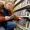 THB photo/John P. Cleary<br /> John Raison of Anderson looks at the description of this DVD as he goes through the racks at Anderson Public Library Tuesday afternoon looking for movies to watch during the snow storm.