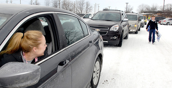 THB photo/John P. Cleary<br /> Sarah Pierce looks out as her son, James, comes walking up along the line of cars waiting to pick up students at Anderson Preparatory Academy Monday afternoon as area schools dismissed classes early due to the pending winter weather moving in with freezing rain, sleet, and snow.