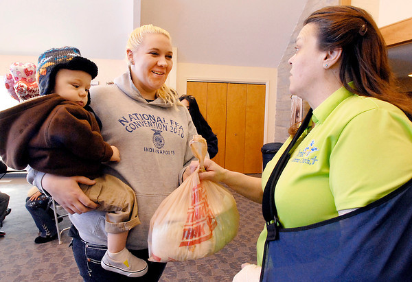 THB photo/John P. Cleary<br /> SuzieDee Pardue, of The Baby Corner at Christ Lutheran Church, hands a bag of diapers to client Brittney Burmeister and her 20 month old son Hunter.<br /> The Baby Corner is open every 3rd Tuesday of the month.