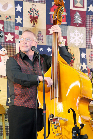 Don Knight / The Herald Bulletin<br /> Mike Lindsey plays base as Common Ground performs during the 25th Annual Snowflake Bluegrass Festival at the Rangeline Community Center on Saturday.
