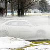 Don Knight / The Herald Bulletin<br /> Motorists drive through standing water caused by a clogged storm drain at the intersection of Graceland and University on Thursday.