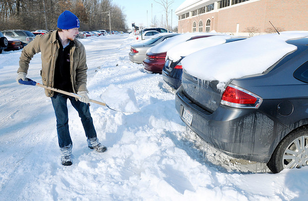 Don Knight / The Herald Bulletin<br /> Luke Monroe, a junior studying Sociology at Anderson University, removes snow from behind a car at AU on Friday. Monroe was part of a small band of students with shovels helping their fellow students dig out their cars before the weekend.
