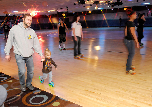Don Knight / The Herald Bulletin<br /> Joe Alexander holds his daughter Trixy's hand as she skates at the Anderson Roll Arena on Saturday. Proceeds from skating Saturday went to Alternatives as part of East Central Roller Derby's fourth annual Open Arms Skate.