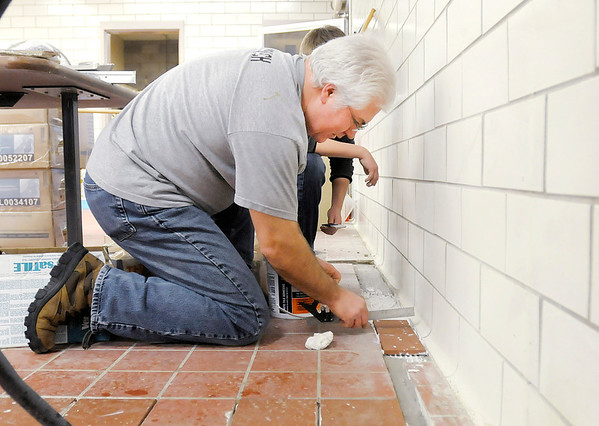 Don Knight / The Herald Bulletin<br /> Scott Silvers installs floor tiles with help from his son Jacob in the kitchen of the former Meadowbrook Elementary School on Friday. Members of the former Lindberg Road Church have been remodeling the school since September to turn it into their new home, Journey Church.