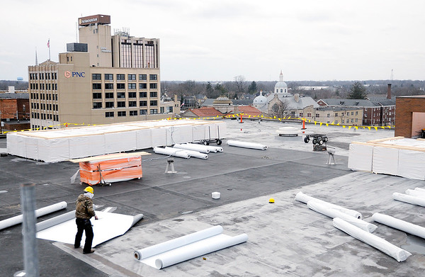 Don Knight | The Herald Bulletin<br /> Crews work on the roof of the Madison County Government Center on Wednesday. County commissioners awarded a contract to Indianapolis Roofing and Sheet Metal, which submitted the lowest of eight bids received at a cost of $187,986.