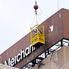 Don Knight | The Herald Bulletin<br /> The First Merchants Bank sign is removed as the bank is moving the branch at 33 W.10th Street to 800 Main St. on Saturday. Tenth Street was closed to accommodate the crane needed to remove the sign.