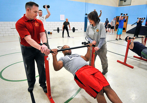 John P. Cleary |  The Herald Bulletin<br /> Area firefighters go through the International Association of Firefighters Peer Fitness Trainer Workshop being held this week in Anderson at the UAW Union Hall. Here Anderson fireman Jeff Adams does pull-ups as IAF workshop instructors Greg Wood and Sue Sheperd assist.