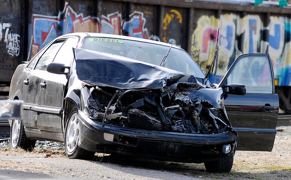 Don Knight | The Herald Bulletin<br /> A Volkswagon sedan sits on the side of Jackson street after a collision between a car and a train at the crossing on Brown Street Tuesday afternoon.