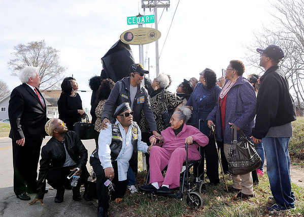 Don Knight   The Herald Bulletin<br /> Mayor Thomas Broderick Jr. and members of Marietta Wright's family look up as a sign honoring Wright is unveiled along a section of 14th Street that was dedicated to her memory in a ceremony on Friday. Wright touched many lives as she gave generously of her time and talent to help the community.