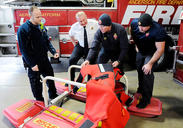 Don Knight | The Herald Bulletin<br /> From left, Kyle Amos, Fire Chief Dave Cravens, Cpt. Brad Corbin and Joey Key look at the features of a cold water rescue suit at AFD Headquarters on Tuesday.