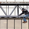 John P. Cleary |  The Herald Bulletin<br /> Workers continue to prepare the facility at 800 Main Street in Anderson for First Merchants Bank to move into in the next several weeks. This worker dangles above the driveway as he works on the bridge that carries the tubes from the drive-through Tuesday morning.